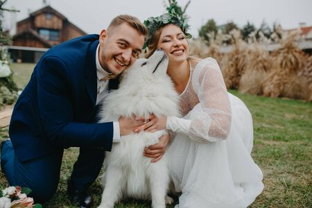 Newlyweds have a fun and play with Samoyed dog on the background of the lawn and the house.