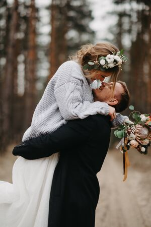 Newlyweds have a fun and embrace at forest path in a coniferous forest among pine trees. Closeup. Reklamní fotografie