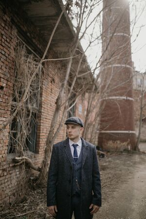 A man posing in the image of an English retro gangster of the 1920s dressed in Peaky blinders style against background of old abandoned building.