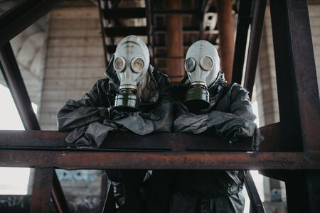 Couple in love stands under bridge in  protective suits and gas masks. Concept of a preventive measures and protection for coronavirus COVID 19 pandemic and other global dangers. Standard-Bild