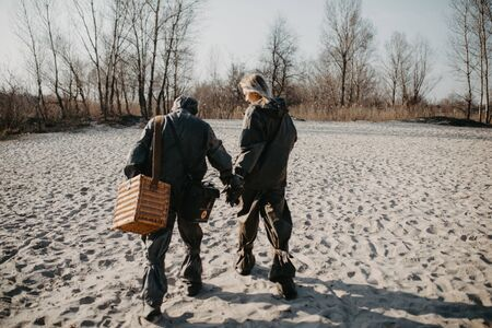 Couple in love walks at beach in  protective suits. Concept of a preventive measures and protection for coronavirus COVID 19 pandemic and other global dangers.