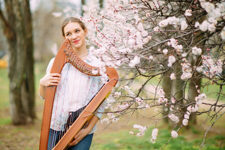 Woman harpist has enjoy and relax at flowering garden and plays harp among blooming apricot trees.