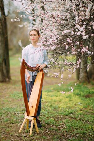 Woman harpist has relax at flowering garden and plays harp among blooming apricot trees.