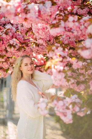 Young woman walks and enjoys in park with blooming sakura trees.