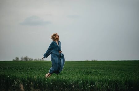 A young woman in blue jacket jumps and has a fun among the green field of wheat. Фото со стока