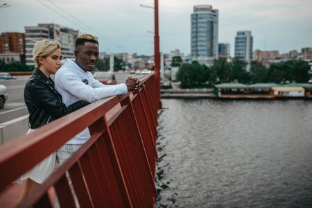 Young interracial couple stands on bridge and hugs against background of river and city. Concept of love relationships and unity between different human races. 版權商用圖片