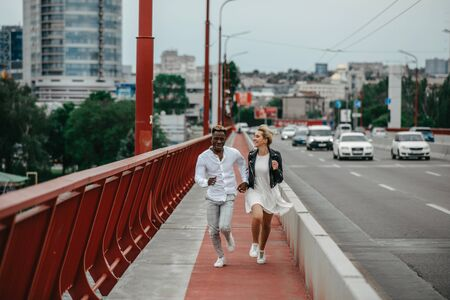 Young interracial couple holds hands, runs on bridge and laughs cheerfully on the background of the city and the road. The concept of love relationships and unity between different human races.
