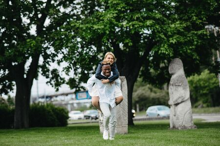 Interracial couple has fun, plays and laughs in park on background of statues Polovtsian women. Concept of love relationships and unity between different human races.