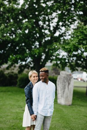 Interracial couple stands and holds hands in park on background of statue Polovtsian woman. Concept of love relationships and unity between different human races.