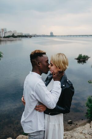Interracial couple kisses and hugs against background of river and city. Concept of love relationships and unity between different human races.