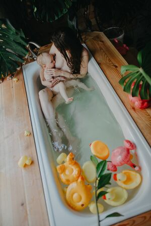 Mother bathes in bathtub and breastfeeds her baby on background of floating toys. Top view.