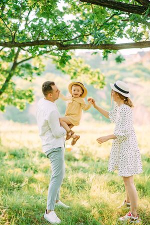 Young parents have a fun and play with their daughter while walking in park.