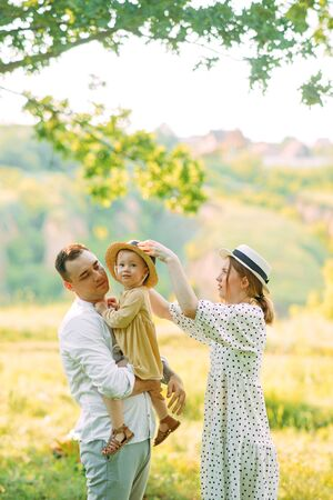 Young parents are with their daughter while walking in park. Archivio Fotografico