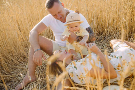 Happy young family with baby rests among yellow wheat field. Stock Photo