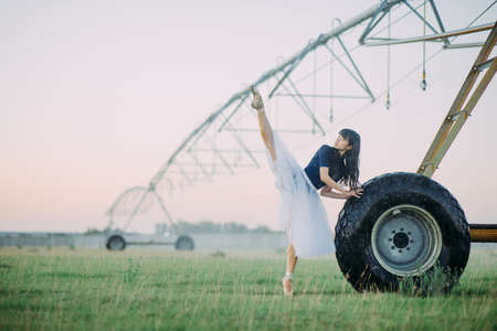 Japanese ballerina in white skirt performs gymnastic twine in field on farm near the wheel of agricultural sprayer.