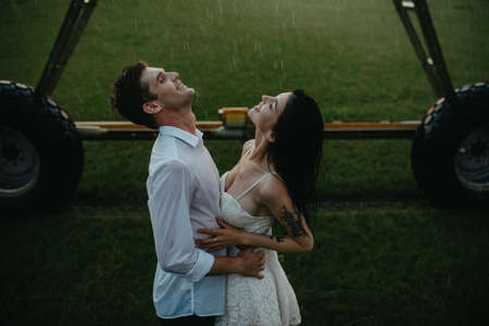 Drenched couple in love stands and embraces under water drops from agricultural sprayer. Stock fotó