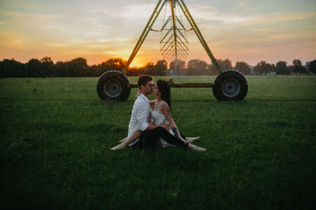 Drenched couple in love kisses and embraces among lawn under water drops from agricultural sprayer at sunset. Stock fotó