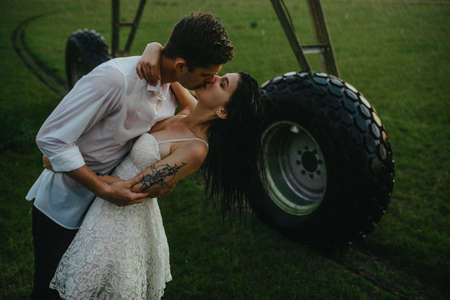 Drenched couple in love kisses and embraces under water drops from agricultural sprayer.