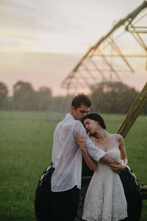 Drenched couple in love stands and embraces under water drops from agricultural sprayer at sunset. Stock fotó