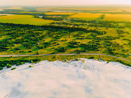 Border of desertification territory and green meadow with river is a result human destructive activity in environment. View from drone.