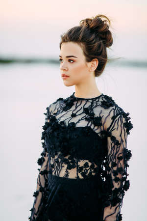 Portrait of woman in lace black dress in desert on background of white sand.
