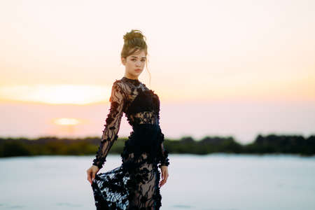 Woman in lace black dress stands and poses in desert on background of sandy landscape at sunset. Stock fotó