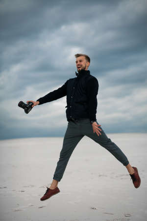 Photographer has a fun, jumps and laughs in desert with digital camera in his hand against background of sand and picturesque sky.