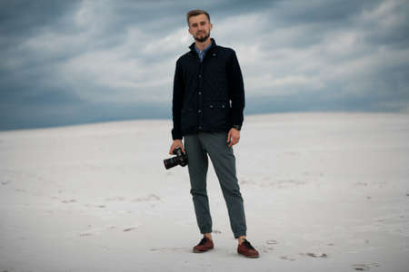 Photographer smiles and stands in desert with digital camera in his hand against background of sand and picturesque sky. Stock fotó