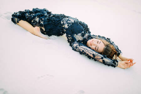 Woman in lace black dress lies in desert on white sand, relaxes and enjoys. Stock fotó