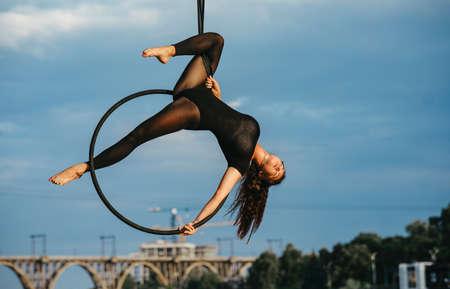 Woman aerialist performs acrobatic elements in hanging aerial hoop against background of bridge, blue sky and trees.