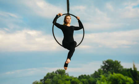 Woman aerialist performs acrobatic elements in hanging aerial hoop against background of blue sky, white clouds and trees.