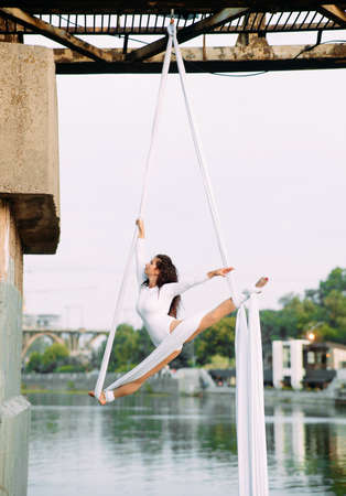 Woman aerialist performs gymnastic split on hanging aerial silk attached to the bridge support against background of sky.