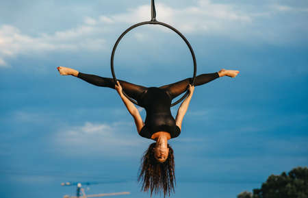 Woman aerialist performs acrobatic element split in hanging aerial hoop against background of blue sky and white clouds. Stock fotó