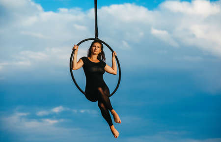 Woman aerialist performs acrobatic elements in hanging aerial hoop against background of blue sky and white clouds.