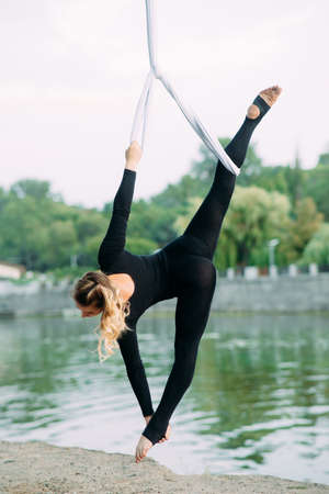 Woman aerialist performs gymnastic split on hanging aerial silk against background of river, sky and trees.