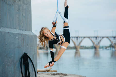 Child girl aerialist performs gymnastic split on hanging aerial silk against background of river. bridge and sky.