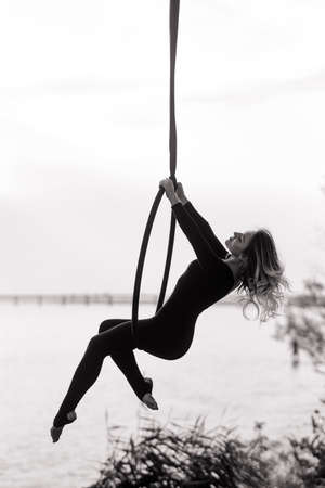 Woman aerialist performs acrobatic elements in hanging aerial hoop against background of river. Black and white image.