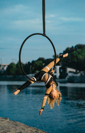 Child girl aerialist performs acrobatic element split in hanging aerial hoop against background of river, blue sky and trees. Stock fotó