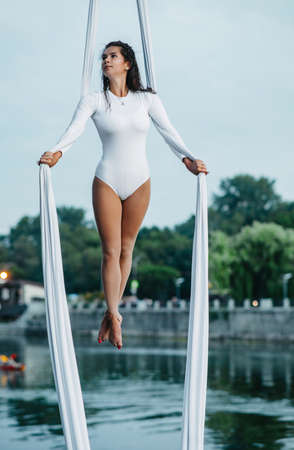 Woman aerialist performs acrobatic tricks on hanging aerial silk against background of river, sky and trees. Stock fotó