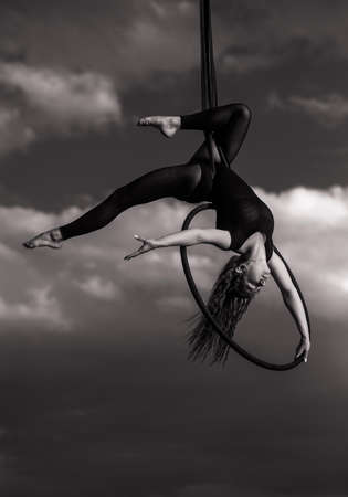Woman aerialist performs acrobatic elements in hanging aerial hoop against background of sky and clouds. Black and white image. Stock fotó