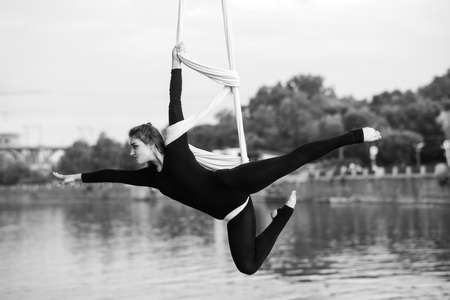 Woman aerialist performs acrobatic tricks on hanging aerial silk against background of river, sky and trees. Black and white image.