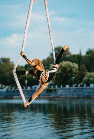 Child girl aerialist performs gymnastic split on hanging aerial silk against background of river, blue sky and trees.