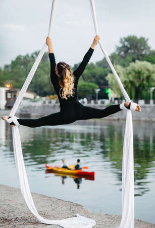 Woman aerialist performs gymnastic split on hanging aerial silk against background of river, floating boat and sky.