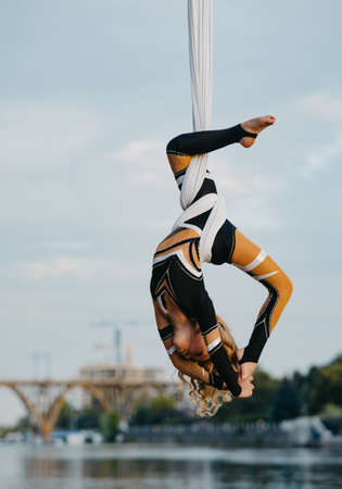 Child girl aerialist performs acrobatic tricks on hanging aerial silk against background of river, sky and bridge.