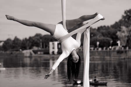 Woman aerialist performs gymnastic split on hanging aerial silk against background of river, sky and trees. Black and white image. Stock fotó