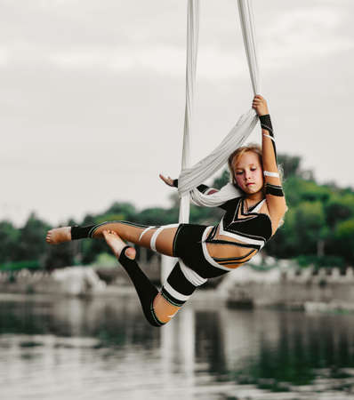 Child girl aerialist performs acrobatic tricks on hanging aerial silk against background of river, sky and trees. Stock fotó