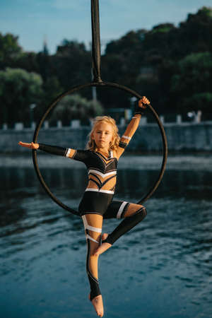 Child girl aerialist performs acrobatic elements in hanging aerial hoop against background of river and trees.
