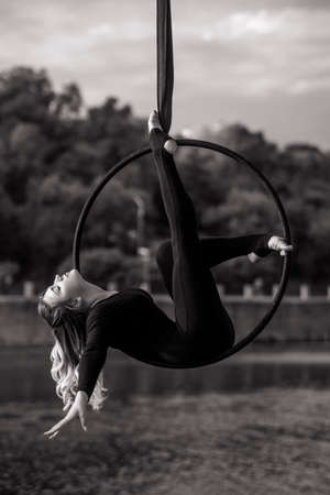Woman aerialist performs acrobatic elements in hanging aerial hoop against background of river, trees and sky with clouds. Black and white image.