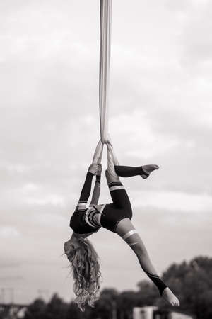 Child girl aerialist performs acrobatic tricks on hanging aerial silk against background of sky and trees. Black and white image.