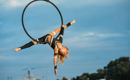 Child girl aerialist performs acrobatic element split in hanging aerial hoop against background of blue sky and white clouds. Stock fotó